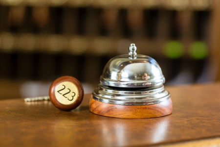 reception room: Reception - Hotel bell and key lying on the desk Stock Photo