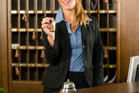 key cabinet: Reception of hotel - desk clerk, woman holding a key in the hand and smiling