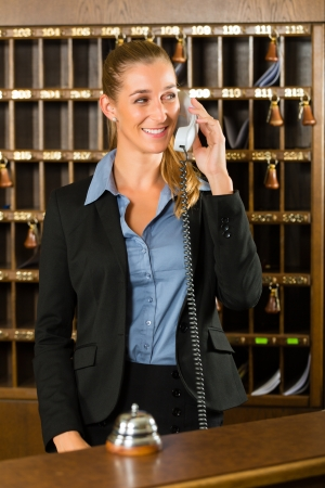 receptionist: Reception of hotel, desk clerk, woman taking a call and smiling