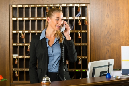 Reception of hotel, desk clerk, woman taking a call and smiling Stock Photo - 17798544