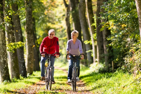 mature men: Senior Man and woman exercising with bicycles outdoors, they are a couple Stock Photo