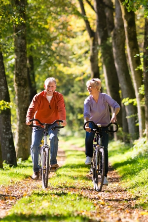 retirement: Senior Man and woman exercising with bicycles outdoors, they are a couple Stock Photo