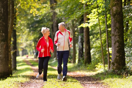 active men: Senior Couple doing sport outdoors, jogging on a forest road in the autumn