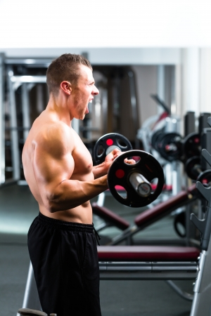 strengthen hand: Strong man - bodybuilder with dumbbells in a gym, exercising with a barbell Stock Photo