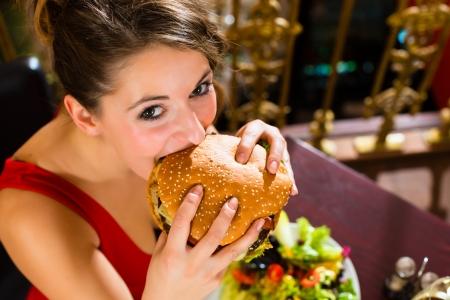 Người phụ nữ trẻ trong một nhà hàng ăn uống tốt ăn một hamburger, cô cư xử không đúng