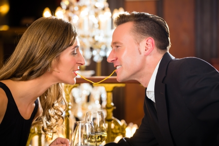happy couple have a romantic date in a fine dining restaurant they eat spaghetti, a large chandelier is in Background photo