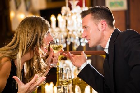 pareja enojada: Pareja tuviere queja en una cita romántica en un restaurante de alta cocina están enojados y gritando, una gran lámpara de araña está en segundo plano