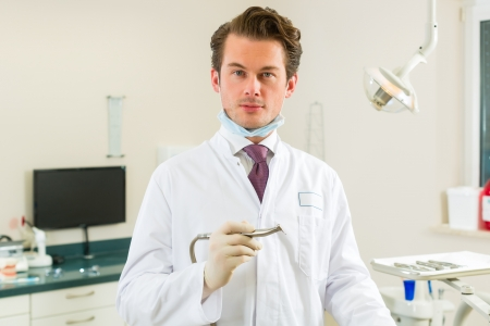Dentists in his surgery holds a drill and looking at the viewer, in the background are tools for a dentist Stock Photo - 17798192
