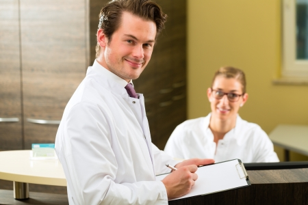 Doctor or dentist with white coat and receptionist standing in a he gives her a clipboard photo