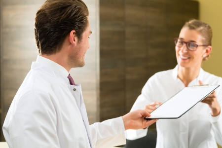 experienced: Doctor or dentist with white coat and clipboard standing in his clinic, the receptionist is in background Stock Photo