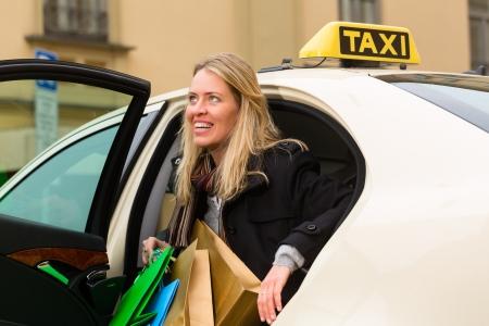 taxi: Mujer joven sale del taxi, que ha llegado a su destino