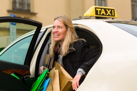 Young woman gets out of taxi, she has reached her destination