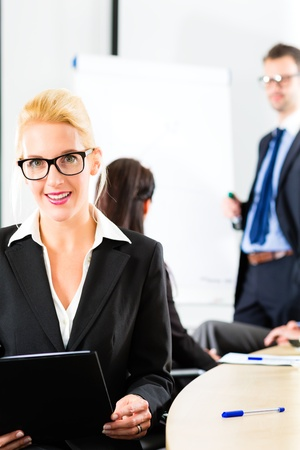 Business - businesspeople have a meeting with presentation in office, they negotiate a contract - Portrait of a businesswoman Stock Photo - 17798198