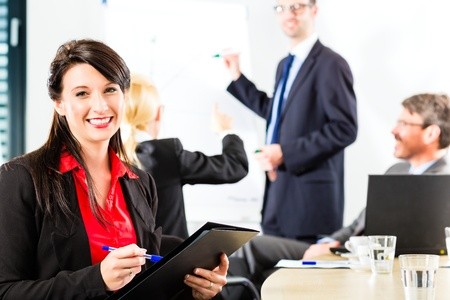 Business - businesspeople have a meeting with presentation in office, they negotiate a contract - Portrait of a businesswoman Stock Photo - 17798361