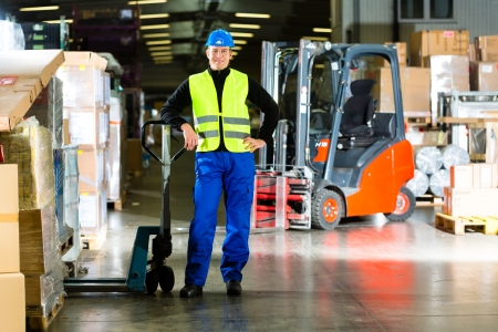 shipper: Warehouseman in protective vest holds a mover, standing beside packages and boxes at warehouse of freight forwarding company- a forklift is in Background