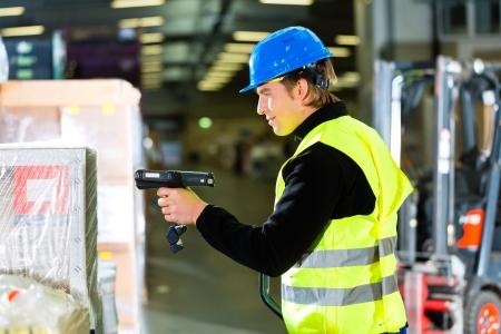 forwarding: Almacenero en chaleco protector utilizando un esc�ner, de pie al lado de paquetes y cajas en el almac�n de la empresa de transporte de carga de una carretilla elevadora est� en segundo plano Foto de archivo