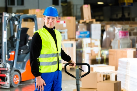 Warehouseman in protective vest pulls a mover with packages and boxes at warehouse of freight forwarding company- a forklift is in Background photo
