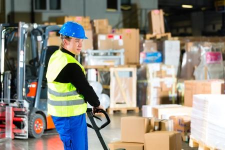 Almacenero en chaleco protector tira de una empresa de mudanzas con los paquetes y cajas en el almacén de la empresa de transporte de carga, un montacargas está en segundo plano Foto de archivo