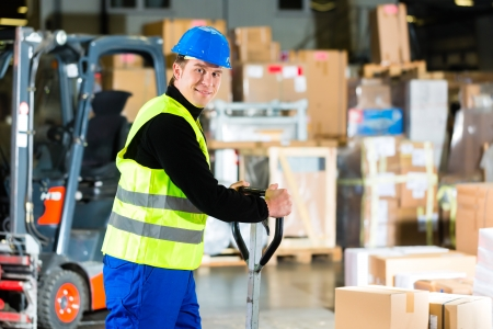 Warehouseman in protective vest pulls a mover with packages and boxes at warehouse of freight forwarding company- a forklift is in Background Stock Photo