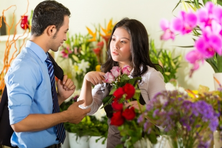Friendly Asian florist or Saleswoman in a flower shop advises a customer photo
