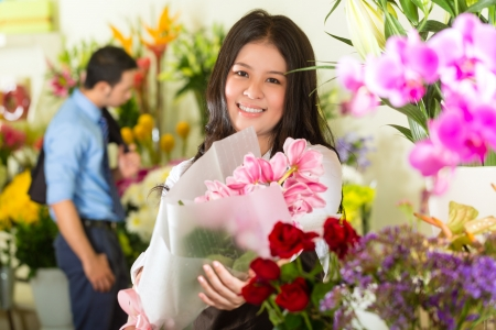Friendly Asian florist or Saleswoman in a flower shop, holding a flower bouquet, in the background is a customer photo
