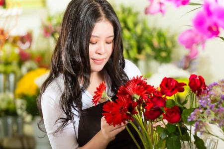 Friendly Asian florist or Saleswoman in a flower shop Stock Photo - 17798490