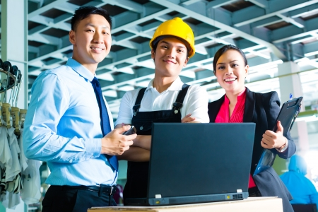 ceo: Chinese Shift supervisor or foreman, together with the owner or CEO and the Manager, standing proud in a factory