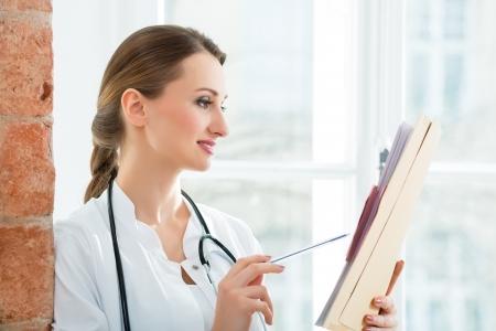 diligente: Médico femenino joven que se coloca en una ventana en la clínica de la lectura de un archivo o expediente