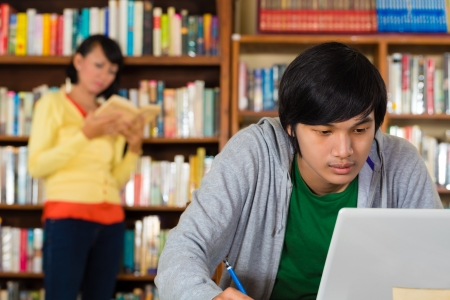 literate: Student - Young Asian man in library with laptop learning, a female student standing in the Background on a shelf reading book Stock Photo