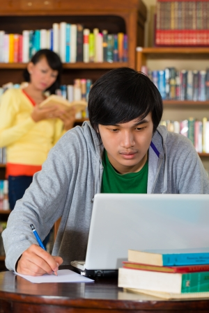Student - Young Asian man in library with laptop learning, a female student standing in the Background on a shelf reading book photo