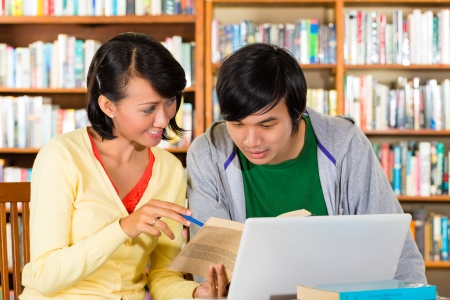 Students - Young Asian woman and man in library with laptop and book learn, they are a learning group photo