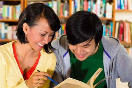 adult indonesia: Students - Young Asian woman and man in library with laptop and book learn, they are a learning group
