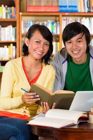 indonesia people: Students - Young Asian woman and man in library with laptop and book learn, they are a learning group