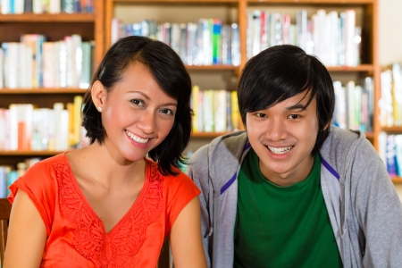 Students - Young woman and man in library with laptop and book learn, they are a learning group Stock Photo - 18064071