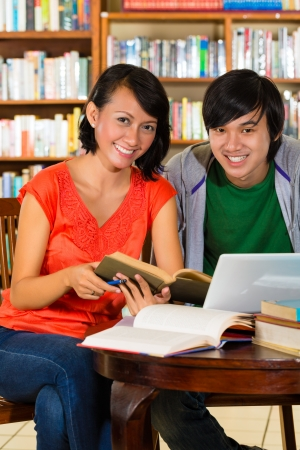 adult indonesia: Students - Young woman and man in library with laptop and book learn, they are a learning group