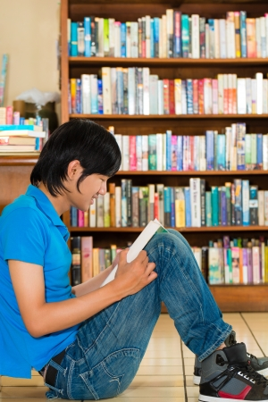 college boy: Student - Young man sits in library on the floor learning reading a book
