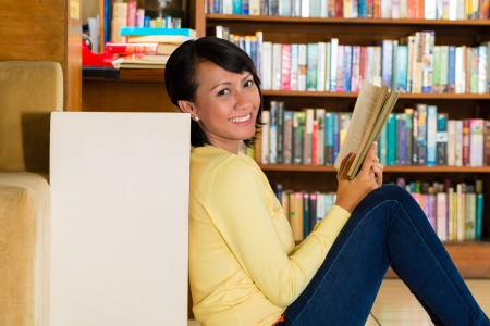 Student - Young woman sits in library on the floor learning reading a book photo