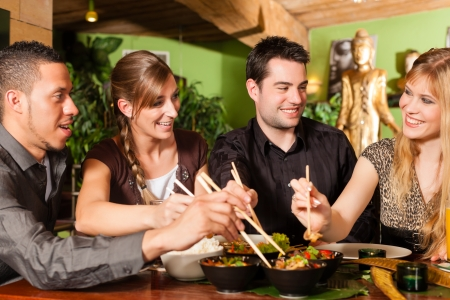 Young people eating in a Thai restaurant, they eating with chopsticks photo