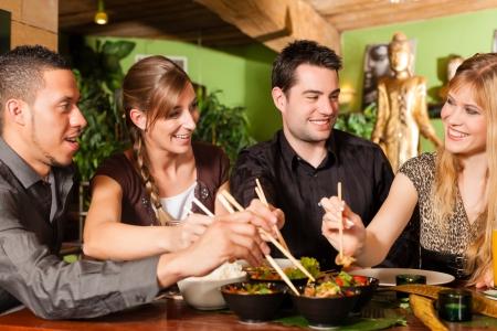 I giovani mangiare in un ristorante tailandese, si mangia con le bacchette