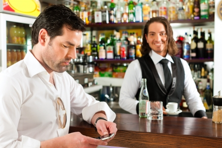 Coffeeshop - barista in cafe with a client, he is drinking coffee photo