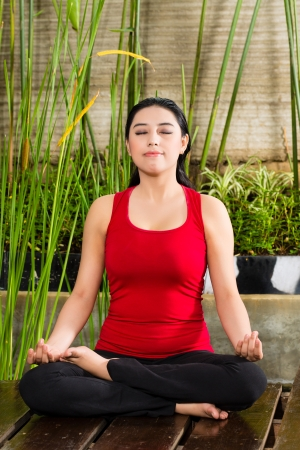 young Asian woman sitting in yoga position while meditating in tropical setting Stock Photo - 18063223