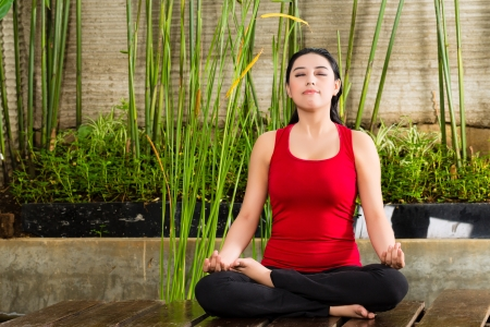 young Asian woman sitting in yoga position while meditating in tropical setting Stock Photo - 18063222
