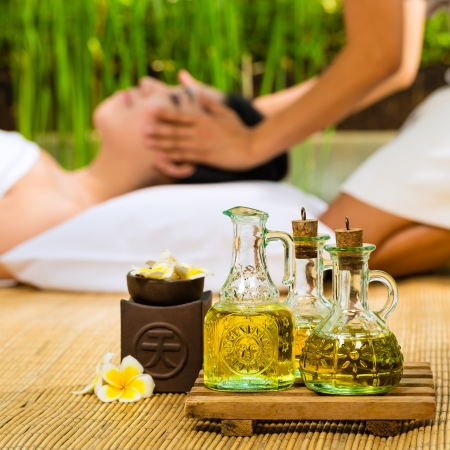 Beautiful Asian woman having a wellness Head massage in a tropical setting and feeling visibly good about it - Essential oils are in the foreground Stock Photo - 18062774