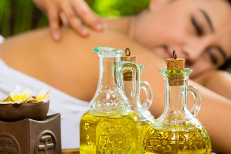 Beautiful Asian woman having a wellness back massage in a tropical setting and feeling visibly good about it - Essential oils are in the foreground Stock Photo - 18063464