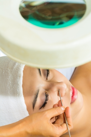 Asian Woman lies in a beauty spa getting a treatment with a comedon compressor Stock Photo - 18064070