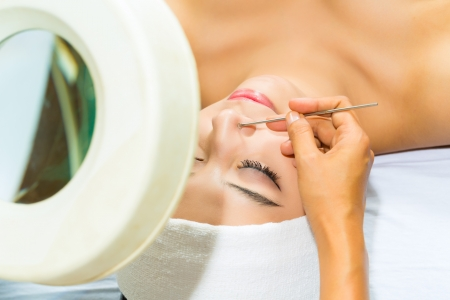 Asian Woman lies in a beauty spa getting a treatment with a comedon compressor Stock Photo - 18062779