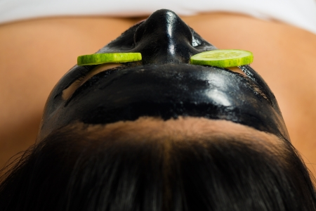 Young Asian Woman in a beauty spa getting a treatment with mask to bleach the skin photo