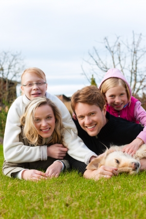 weekend activities: Family, father, mother and daughters, sitting together with their dog on a meadow, they are laughing and have fun