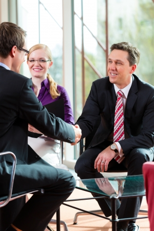 interviewing: Man having an interview with manager and partner employment job candidate hiring resume CEO work business shaking hands Stock Photo