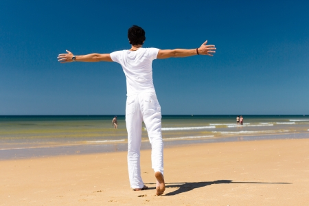 beachwear: Handsome man on the ocean beach enjoying his summer vacation, arms stretched out towards the sun as a symbol of freedom